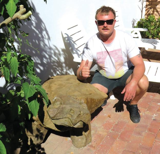 Hier is Hannes Oosthuizen saam met Bergie, die sandsteenbeeld wat hy vir Terrapin Garden, 'n gastehuis op Oudtshoorn, ontwerp en installeer het.     Foto: Ilze-Mari Gründling