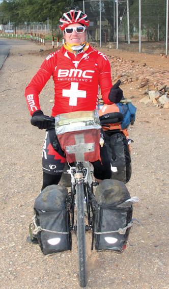 Pascal Bärtschi op sy swaar gelaaide fiets waarmee hy die wêreld deurkruis.