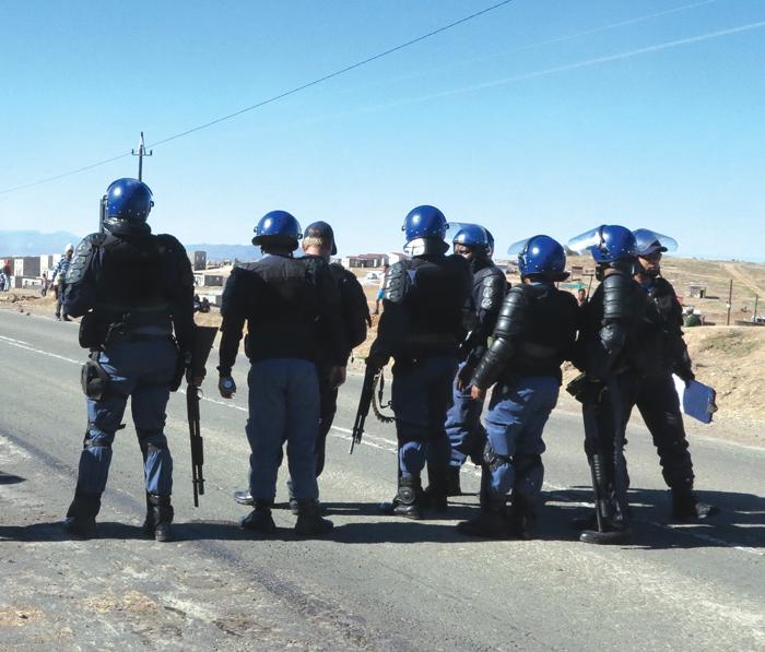 'n Ongewone gesig op Oudtshoorn. Lede van die polisie se onluste-eenheid arriveer Maandag op die De Rustpad (links) waar betogers die pad met klippe en brandende binnebande versper het (regs) en geweier het om uiteen te gaan.