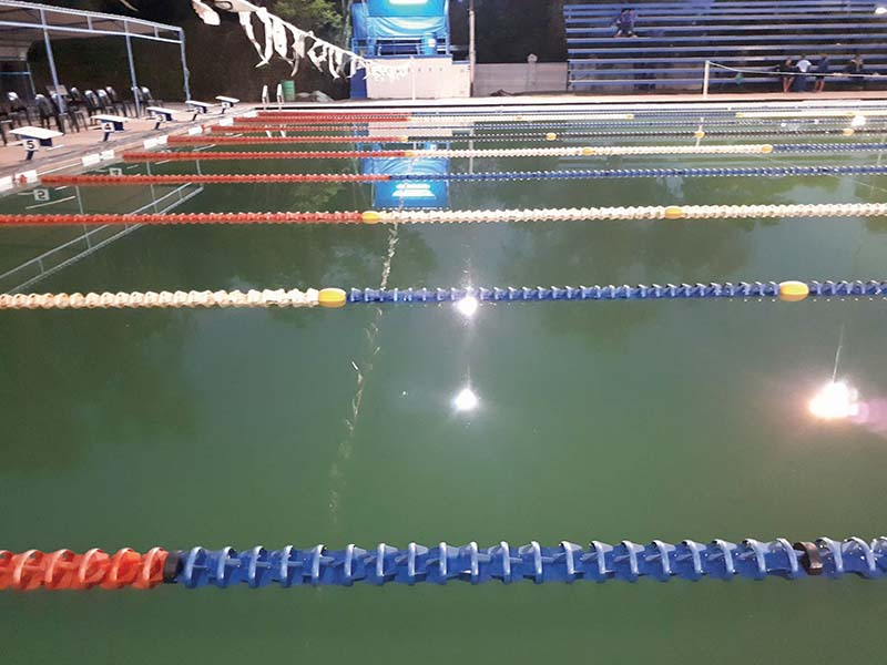 Oudtshoorn se groen swembad. Bo is die NA Smit Swembad Dinsdagaand net voor die aanvang van die SWD Tweekamp-swemproewe. Die foto regs is die middag geneem enkele ure voordat die byeenkoms begin het. Dit toon die groen water en erg gekraakte sementblokke langs die swembad. Foto's: Liesel le Roux