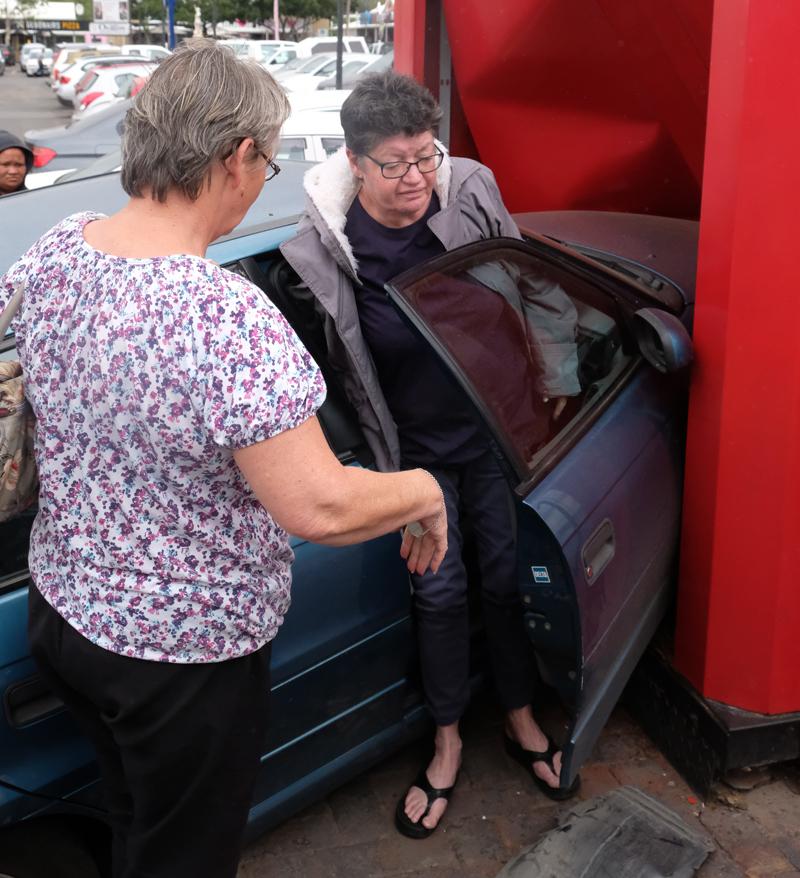 Die geskokte bestuurder klim uit haar Opel nadat sy daarmee Absa Outoteller op die parkeerterrein van die Queen's Mall in Voortrekkerweg, Oudtshoorn vasgery het.
