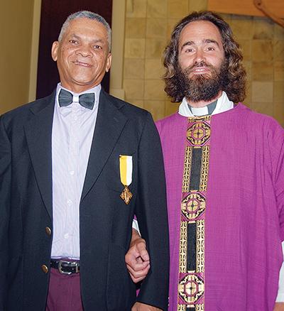 Vader Enrico Parry, kanselier van die Katolieke bisdom Oudtshoorn, saam met Willie Lamont aan wie hy 'n medalje oorhandig het.
