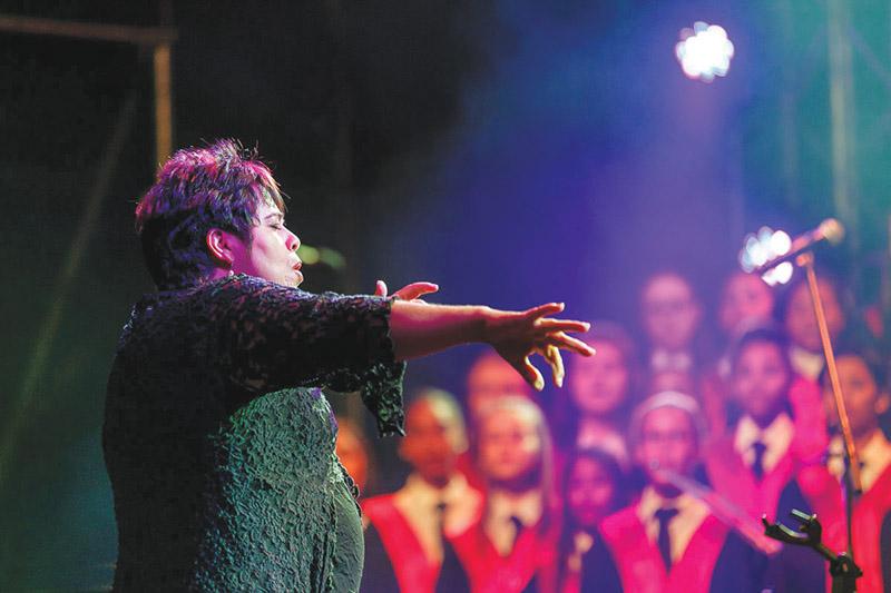Elmine Bester, afrigter van die Ad Astra-koor van die Hoërskool Oudtshoorn, in aksie! Dié koor tree Sondagaand op in die opelug-produksie Boontoe - Engelstemme op die Huisgenoot-verhoog saam met van die land se voorste kunstenaars. Meer oor Elmine en die koor op bl 3. Foto: Hans van der Veen