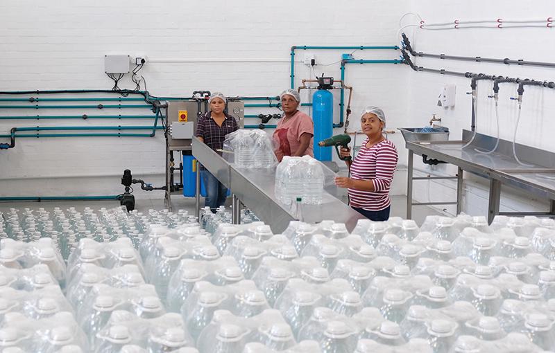 MGWater se watersuiweringsaanleg waar die gesuiwerde water gebotteleer en verpak word. Besig met die verpakkingswerk is van links Caroline Tarentaal, Lize Coetzee en Sonja Makshella.