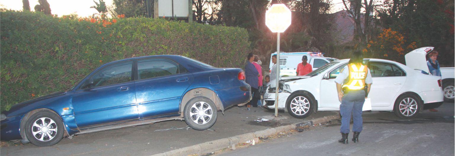 Een motor in heining, ander teen stopteken na botsing op straathoek